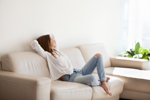 happy woman relaxing on couch in clean house