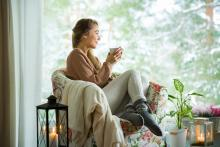 woman enjoying cup of tea in cozy room inside home