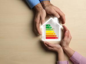 Two sets of hands holding house with energy audit