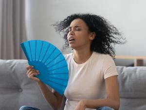 woman at home fanning herself, hot summer house
