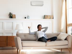 woman at home adjusting mini split on wall