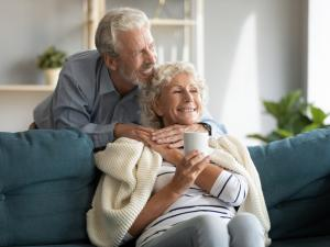 older couple together at home warm and cozy on the couch